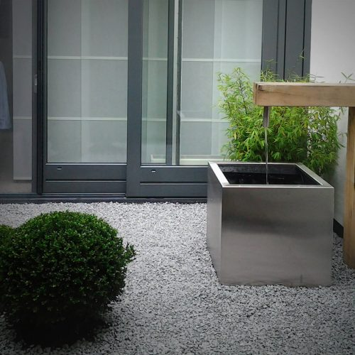 Minimalistische patio met RVS waterelement en buxusbollen